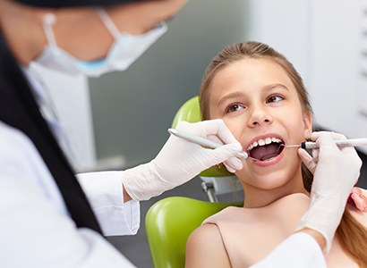dentist checking little girls smile