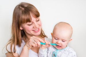 Mother brushing baby's teeth