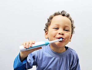 Toodler brushing teeth with toothpaste