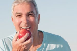 man biting into an apple with implant-retained denture